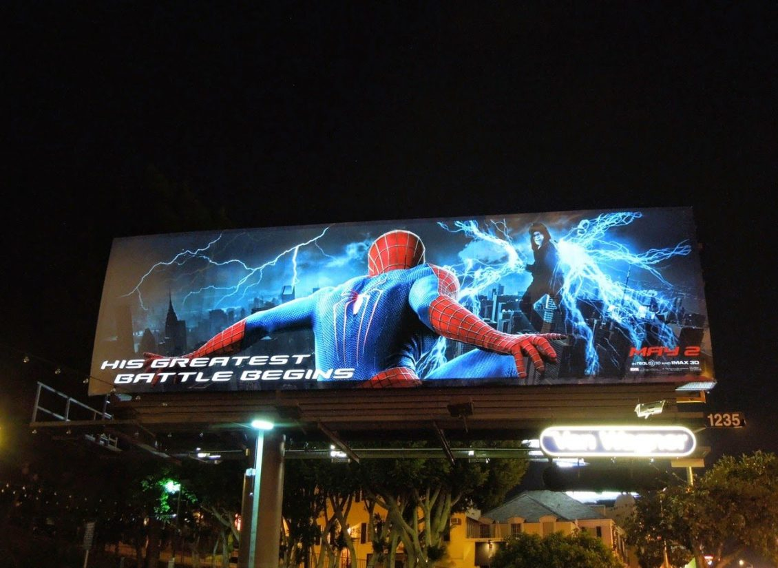 Lighted billboard with white lighted text advertising Spiderman at night